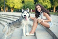 Café de hielo de consumición de la muchacha y el jugar con su perro fornido en el parque Foto de archivo libre de regalías