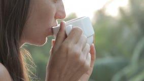 Café de jeune femme attirante ou thé potable sur le balcon, plan rapproché clips vidéos