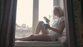 Café de jeune femme et smartphone potables d'utilisation tout en se reposant au filon-couche de fenêtre à la maison banque de vidéos