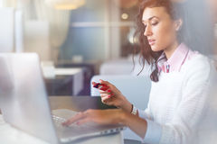 Café de la empresaria joven y ordenador portátil de consumición con en el café que hace las compras en línea, tarjeta de crédito  Foto de archivo libre de regalías