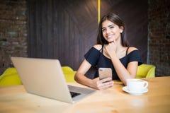 Café de la forma de vida, mujer que usa el smartphone para la información de la búsqueda en tienda del café Fotografía de archivo libre de regalías