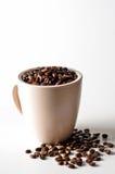 Café de la haba entera en la taza aislada en blanco Imagen de archivo libre de regalías