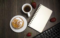 Café de la mañana con el buñuelo para el encargado Hoja vacía del cuaderno Teclado Fresas en un fondo oscuro Foto de archivo