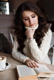 Café de la mañana, disfrute, ella la cerró los ojos Muchacha asombrosa que lee un libro y una sonrisa Foto de archivo
