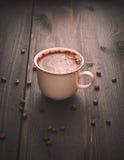 Café de la mañana en una taza blanca en una tabla marrón con las flores y el canela Foto de archivo libre de regalías