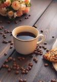 Café de la mañana en una taza blanca en una tabla marrón con las flores y el canela Foto de archivo