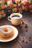 Café de la mañana en una taza blanca en una tabla marrón con las flores y el canela Fotografía de archivo