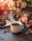 Café de la mañana en una taza blanca en una tabla marrón con las flores y el canela Fotos de archivo