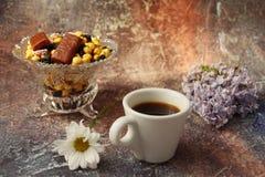 Café de la mañana a toda prisa: una taza de café, de flores en un florero, de frutas secadas y de dulces en un florero, una vela  foto de archivo