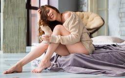 Café de la mujer feliz o té y sonrisa de consumición mientras que se sienta en casa en dormitorio temprano por la mañana foto de archivo libre de regalías