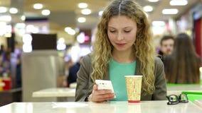 Café de la mujer joven o té y usar de consumición felices el teléfono móvil en una cafetería metrajes
