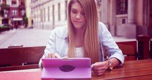 Café de la mujer joven/té y tableta de consumición felices con almacen de metraje de vídeo