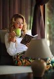 Café de la mujer joven y libro de lectura de consumición felices en el sofá Imagen de archivo