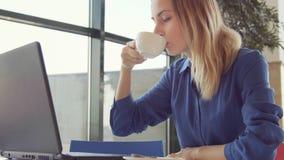 Café de la mujer joven y tableta de consumición felices con en una cafetería metrajes