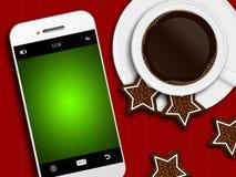 Café de la Navidad, pan de jengibre y teléfono móvil mintiendo en tableclo Fotografía de archivo