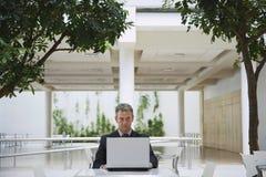 Café de la oficina de Using Laptop At del hombre de negocios Fotos de archivo