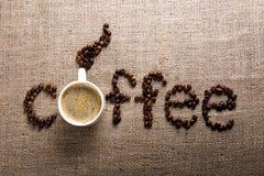 CAFÉ de la palabra de los granos y de la taza de café Foto de archivo libre de regalías