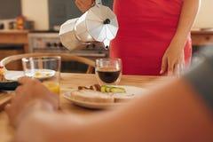 Café de la porción de la mujer en la mesa de desayuno Imagen de archivo libre de regalías