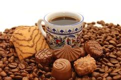 Café de la taza con las galletas y los chocolates Imágenes de archivo libres de regalías