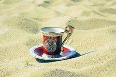 Café de la taza en la arena Imágenes de archivo libres de regalías