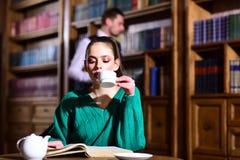 Café de littérature avec la fille et l'homme mignons la femme dans la bibliothèque a lu le livre au café potable de théière de la Image stock