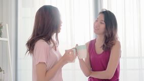 Café de los pares felices lesbianos de las mujeres asiáticas jovenes que habla y de consumición en dormitorio en casa metrajes