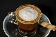 Café de Macchiato del italiano con el rollo de la oblea foto de archivo