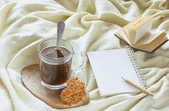 Café de matin avec des biscuits, livre, crayon sur le plaid jaune Photographie stock libre de droits
