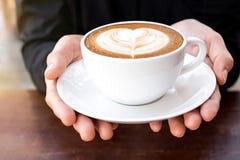 Café de matin, mains tenant la tasse de latte chaud de café avec le coeur Photo libre de droits