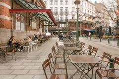 Café de rue avec les meubles en acier, les personnes potables et les vieux bâtiments avec des restaurants Photo stock