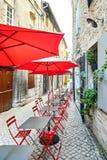 Café de rue d'été avec les parapluies et les chaises rouges photos stock