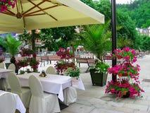 Café de rue sous l'auvent, tables vides avec les tableclothes blancs au temps de dîner Rue confortable verte photos libres de droits