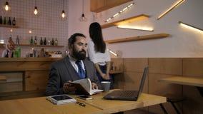 Café de servicio de la camarera al hombre de negocios en el café almacen de metraje de vídeo
