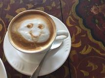 Café de sourire de cappuccino sur le Tableau rouge en bois de conception indienne photographie stock