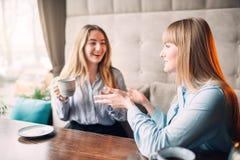 Café de sourire de deux boissons d'amies en café Image stock