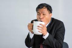 Café de trabajo duro /Isolate de Fatigue Drinking del hombre de negocios imagenes de archivo