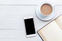 Café de vue supérieure, smartphone et livre vide sur la table en bois blanche Photo stock
