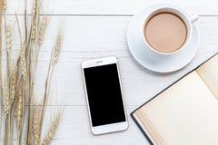Café de vue supérieure, smartphone et livre vide sur la table en bois blanche Photos stock