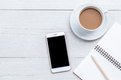 Café de vue supérieure, smartphone et livre vide sur la table en bois blanche Images stock