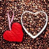 Café del amor en el día de tarjeta del día de San Valentín. Granos de café asados con rojo él Imagen de archivo