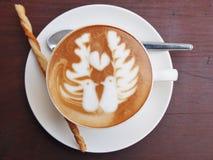 Café del arte del Latte en el escritorio de madera Fotografía de archivo
