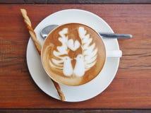 Café del arte del Latte en el escritorio de madera Imágenes de archivo libres de regalías