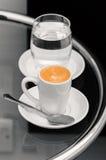 Café del café express y vidrio de agua en la tabla superior Foto de archivo libre de regalías