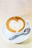 Café del Cappuccino con el gráfico del corazón en la taza blanca Foto de archivo