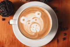 Café del capuchino con arte del latte bajo la forma de primer del oso en una tabla de madera El concepto de café en el café fotos de archivo