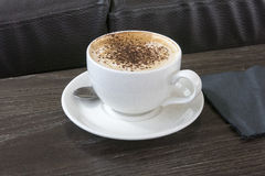 Café del capuchino en la tabla de la cafetería Foto de archivo libre de regalías