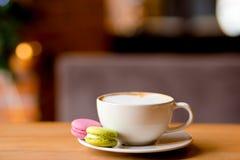 Café del capuchino en la taza blanca con los macarrones coloridos servidos en la tabla de madera foto de archivo libre de regalías