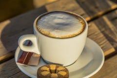 Café del capuchino en una taza blanca con cinnamone y las galletas Imagen de archivo libre de regalías