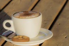 Café del capuchino en una taza blanca con cinnamone y las galletas Fotos de archivo libres de regalías