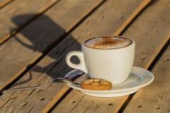 Café del capuchino en una taza blanca con cinnamone y las galletas Foto de archivo libre de regalías